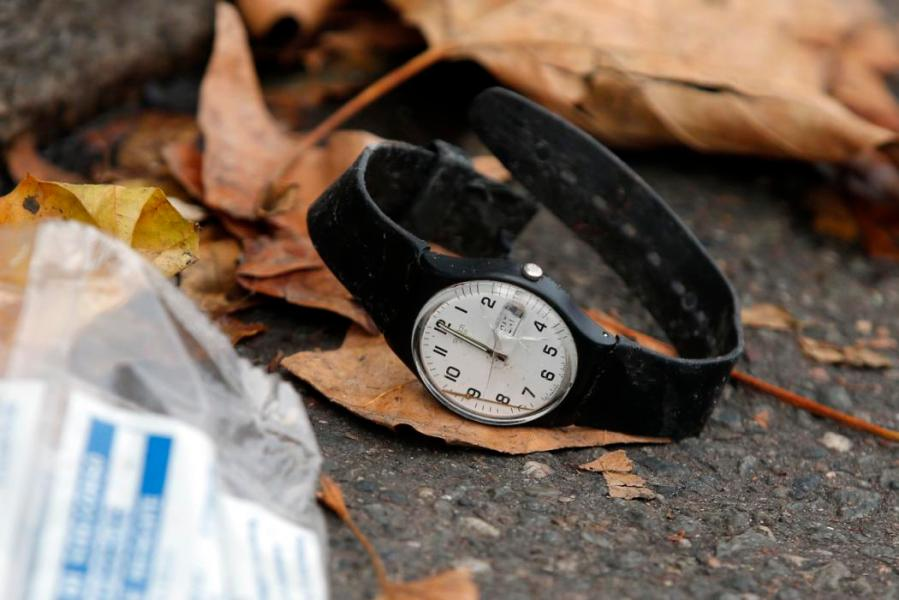 A watch lays on the ground outside the Bataclan concert hall, Saturday, Nov. 14, 2015 in Paris. French President Francois Hollande said more than 120 people died Friday night in shootings at Paris cafes, suicide bombings near France's national stadium and a hostage-taking slaughter inside a concert hall. (AP Photo/Christophe Ena)