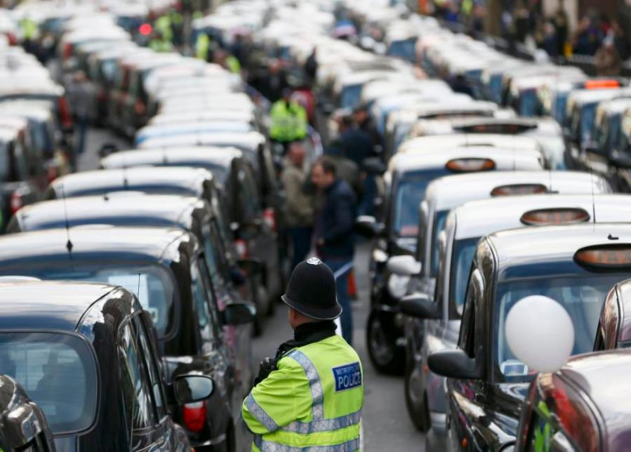 A police officer stands between rows of taxis during a protest by London cab drivers against Uber in central London, February 10, 2015 REUTERS/Stefan Wermuth TPX IMAGES OF THE DAY