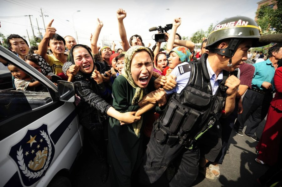 Ethnic Uygur women grab a riot policemen as they protest in Urumqi in China's far west Xinjiang province on July 7, 2009. Police fired clouds of acrid tear gas to disperse thousands of Han Chinese protesters armed with makeshift weapons, as chaos gripped this flashpoint city riven by ethnic tensions. Thousands of heavily armed police deployed across Urumqi, the capital of China's remote northwest Xinjiang region, but tensions spiked dramatically following weekend rioting that claimed at least 156 lives. TOPSHOTS AFP PHOTO/Peter PARKS (Photo credit should read PETER PARKS/AFP/Getty Images)