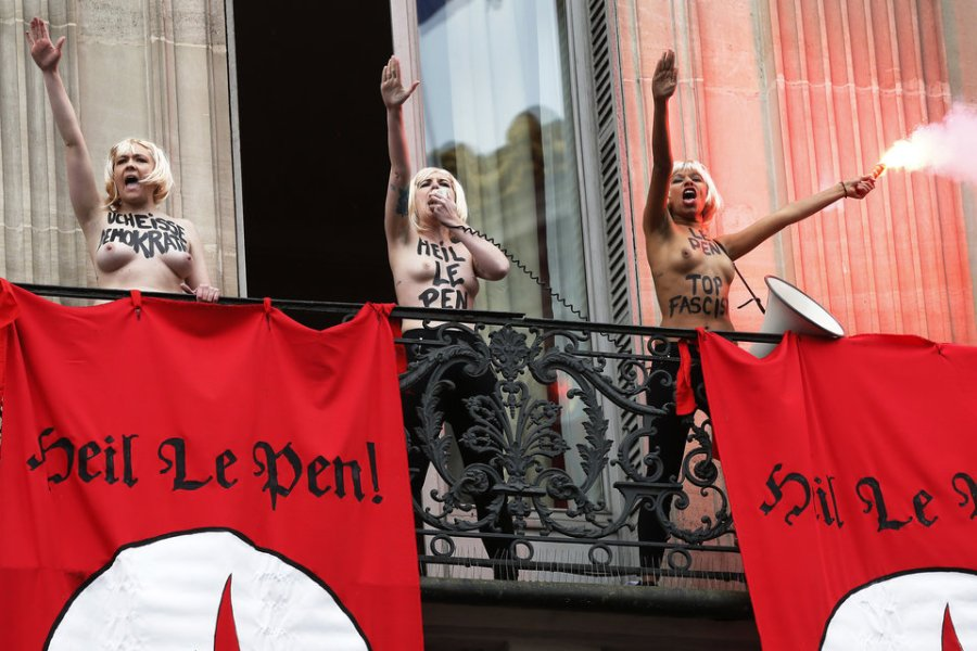 "Topless Femen activists perform the Nazi salute near flags reading ""Heil Le Pen"" as they demonstrate on a balcony against France's far-right Front National (FN) political party during an FN rally in honour of Jeanne d'Arc (Joan of Arc) taking place just below in Paris on May 1, 2015. AFP PHOTO / THOMAS SAMSON (Photo credit should read THOMAS SAMSON/AFP/Getty Images)"