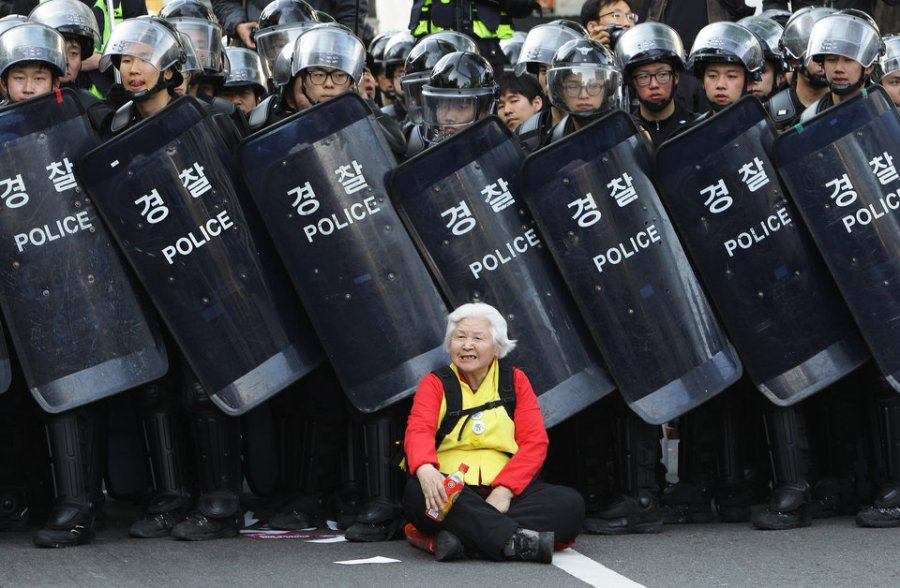 SEOUL, SOUTH KOREA - APRIL 24: A woman sits in front of riot police blocking the road to protect protesters during the anti-government protest on April 24, 2015 in Seoul, South Korea. Korean Confederation of Trade Unions (KCTU) went on a general strike in protest against the South Korean government's policy, including reformation of the labor market and public pension system. The rally was also joined by other civic groups in Seoul and families of Sewol accident victims. (Photo by Chung Sung-Jun/Getty Images)